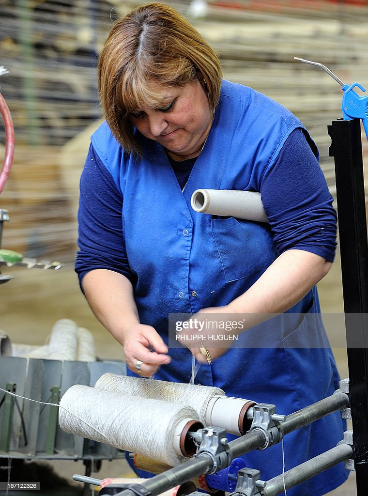 An employee of the Lemaitre Demeestere company works with a linen coil on April 16, 2013 in Halluin, northern France.