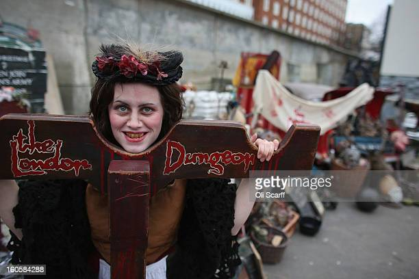 An employee of 'The London Dungeon' poses with props previously used at the attraction which are to be sold at a car boot sale in Pimlico as the...