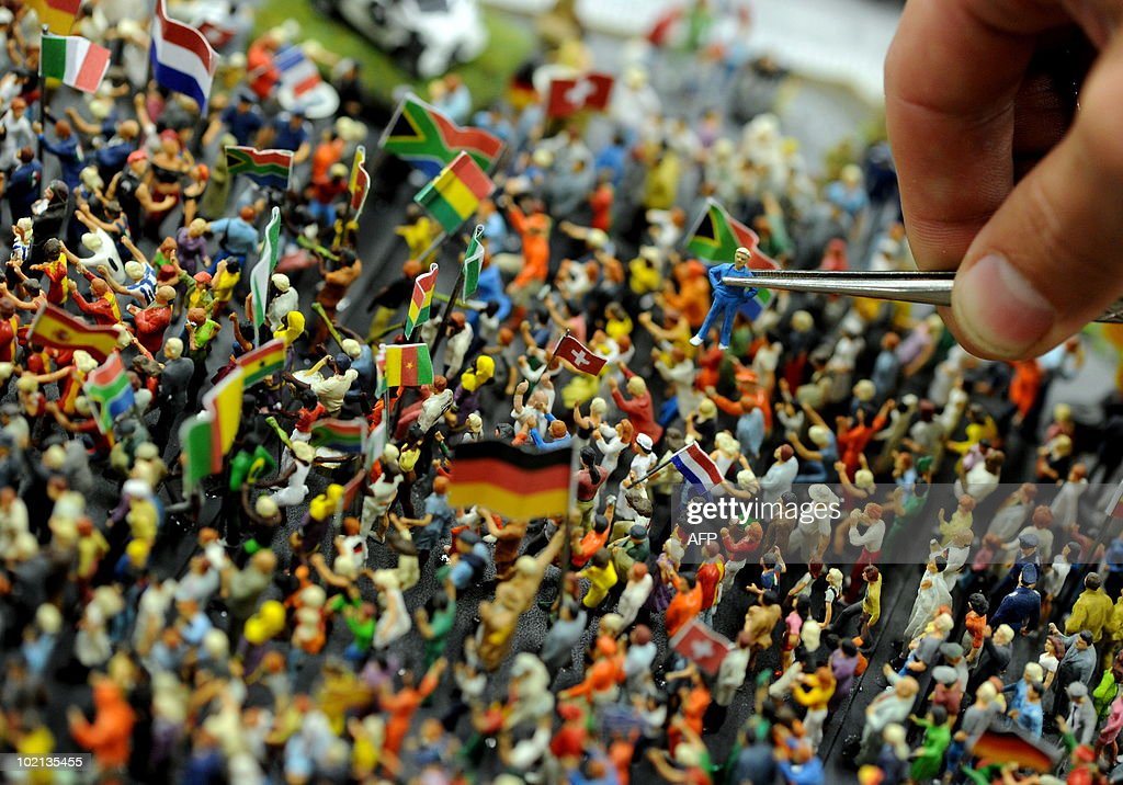 An employee of the 'Miniatur Wunderland' (Miniature Wonderland) holds a figure of a model making Public Viewing with tweezers in Hamburg, northern Germany on June 9, 2010. During the time of the FIFA World Cup 2010, the Miniatur Wunderland exhibits model makings of fans, Public Viewings and motorcades.