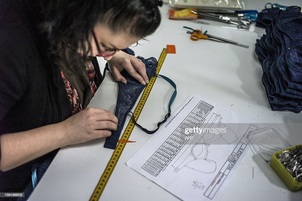 An employee of the new lingerie company 'Les Atelieres' works in Villeurbanne, centraleastern France, on January 14, 2013. 'Les Atelieres' was founded after the recent decline of the lingerie company Lejaby and employs six former workers of Lejaby, amongst its 26 employees. It launched production today. AFP PHOTO / JEFF PACHOUD