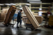 An employee of the OGF company transports wooden coffins on trolleys on October 29 2012 in Reyrieux central eastern France The coffin industry...