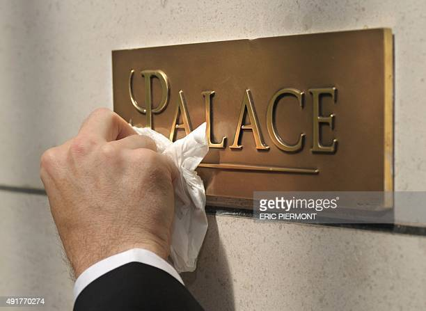 An employee of the Paris fivestar hotel Bristol cleans on May 5 2011 their new plaque reading 'Palace' the French highest rating for hotels A list of...