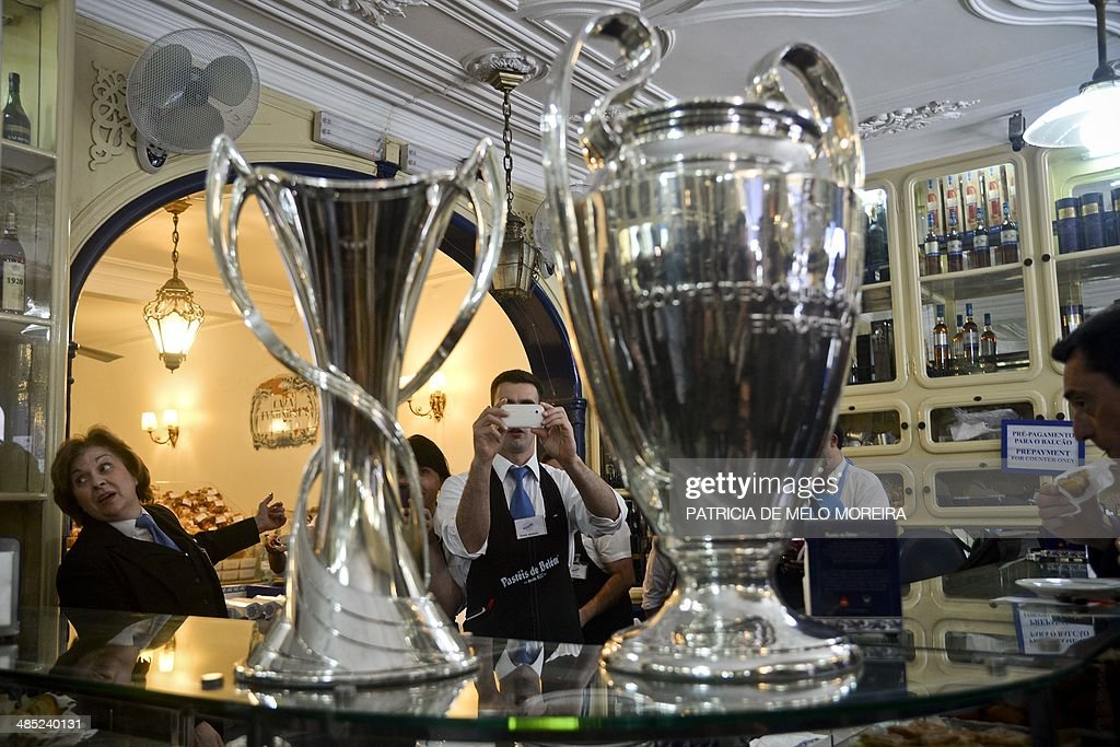 An employee of the pastry 'Pasteis de Belem' takes pictures of the UEFA Champions League trophies during the trophy handover in Lisbon on April 17, 2014. The UEFA Champions League football final will take place at the Luz Stadium in Lisbon on May 24, 2014. AFP PHOTO / PATRICIA DE MELO MOREIRA