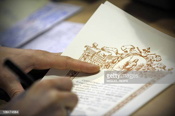 An employee of the Pilgrim Office fills a 'Compostela' the certificate confirming the completion of the pilgrimage on October 27 end of the Way of...