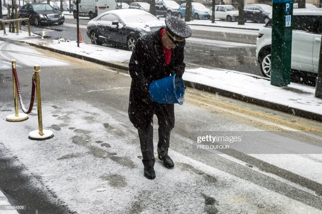 An employee of the Plaza Athenee hotel spreads salt on the pavement on March 12, 2013 in Paris during a heavy snow storm on France. More than 68,000 homes were without electricity in France and hundreds of people were trapped in their cars, officials and weather services said today. Twenty-six regions in northwest and northern France were put on orange alert because of heavy snowfalls, which Meteo France said were 'remarkable for the season because of the expected quantity and length of time'. AFP PHOTO / FRED DUFOUR