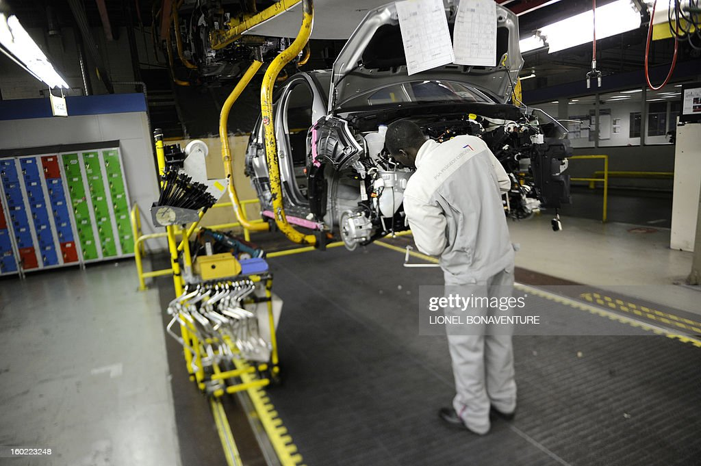 An employee of the PSA Peugeot Citroen carmaker plant of Aulnay-sous-Bois, a Paris' suburb, is at work on the assembly line on January 28, 2013 in Aulnay-sous-Bois. AFP PHOTO LIONEL BONAVENTURE