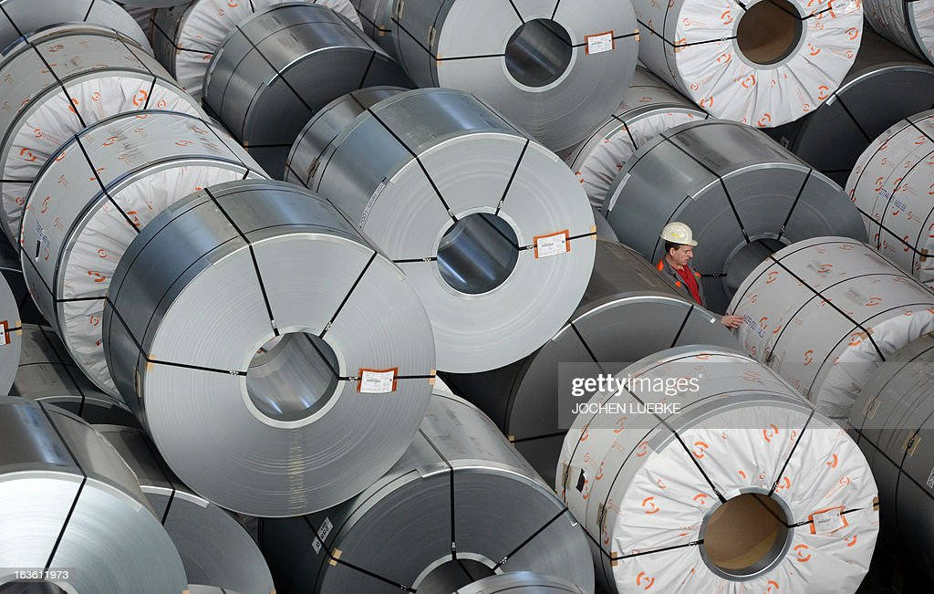 An employee of the Salzgitter AG stands between coils at the company's plant in Salzgitter, central Germany, on March 13, 2013. Salzgitter AG is Germany's number-two steel maker.