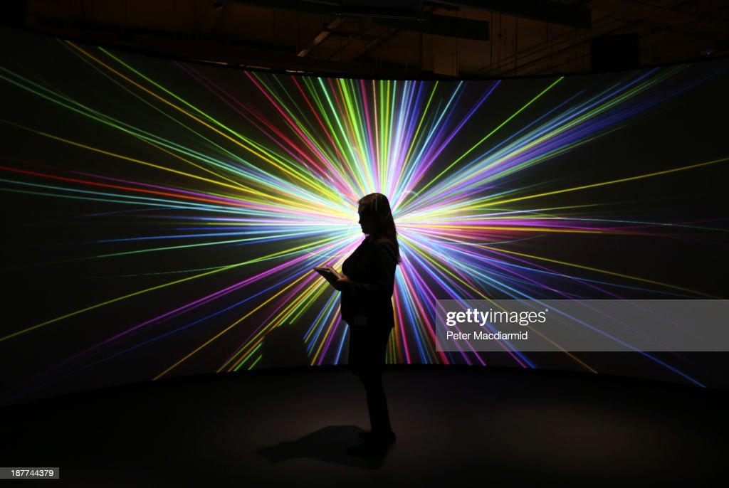 An employee of the Science Museum stands in front of a video projection showing the workings of the Large Hadron Collider (LHC) at the 'Collider' exhibition on November 12, 2013 in London, England. At the exhibition, which opens to the public on November 13, 2013 visitors will see a theatre, video and sound art installation and artefacts from the LHC, providing a behind-the-scenes look at the CERN particle physics laboratory in Geneva. It touches on the discovery of the Higgs boson, or God particle, the realisation of scientist Peter Higgs theory.