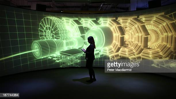An employee of the Science Museum stands in front of a video projection showing the workings of the Large Hadron Collider at the 'Collider'...