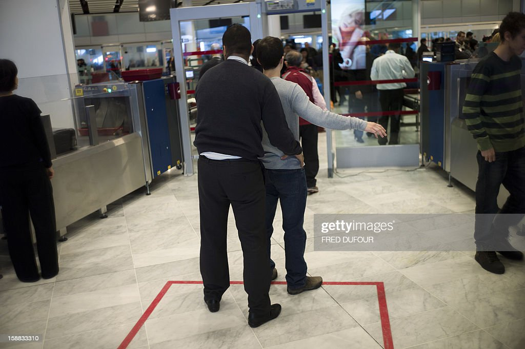An employee of the security controls a traveller at the Charles de Gaulle airport on December 31, 2012 in Roissy.