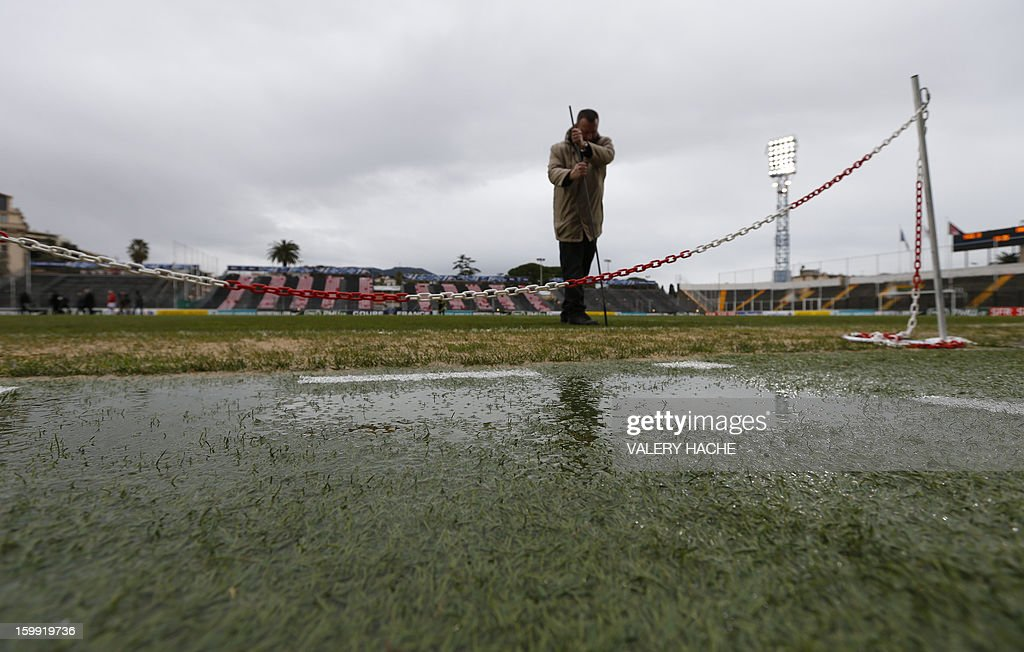 An employee of the stadium examines the field damaged by heavy rains some hours before the French Cup football match Nice vs Nancy, on January 23, 2013 at the Ray stadium in Nice. The local authority in charge of wheather forecast will decide if the match takes place.