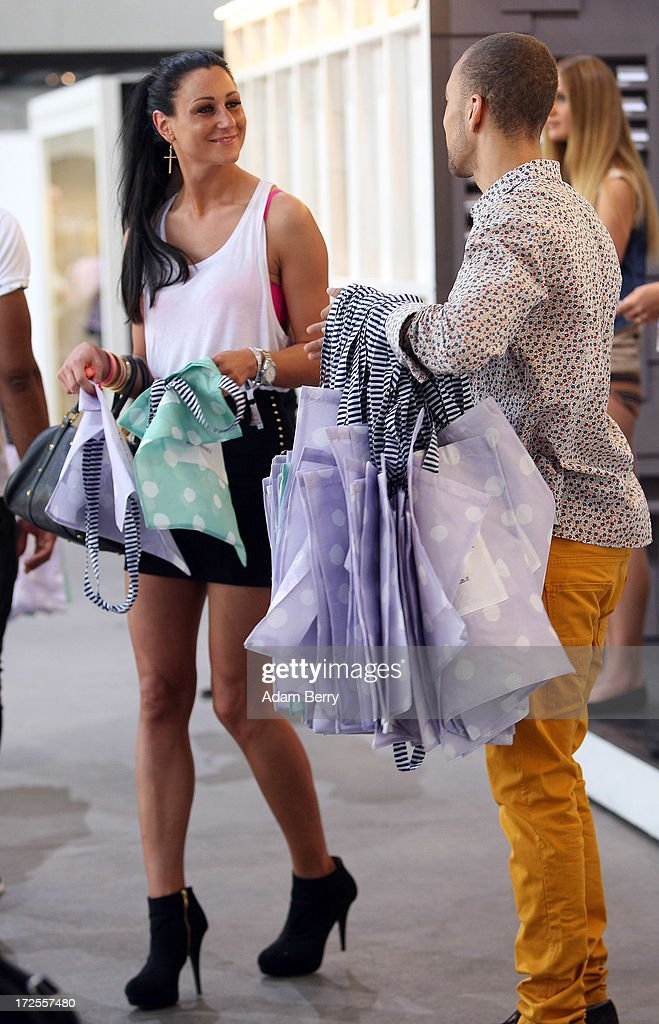 An employee of the stand by the brand Sylvian Heach hands out a free tote bag to a visitor at the Bread and Butter trade show at the former Tempelhof airport during Mercedes-Benz Fashion Week in Berlin on July 3, 2013 in Berlin, Germany.