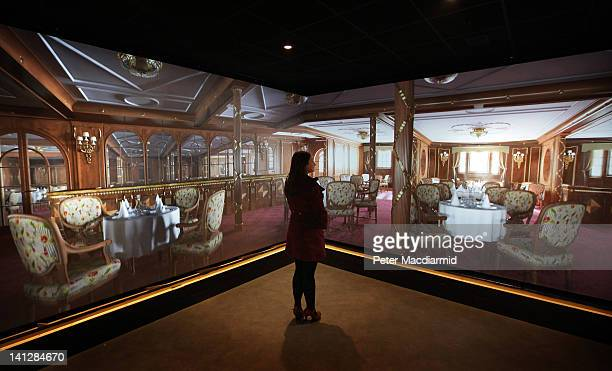 An employee of The Titanic Belfast attraction stands in front of screens showing computer generated images of a restaurant on The Titanic on March 13...