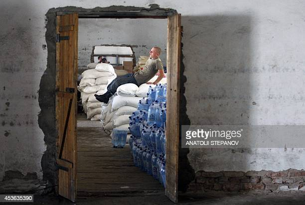 An employee of the Ukrainian Emergency Ministry sits on food sacks near packs of water bottles brought by the Ukrainian humanitarian convoy on August...