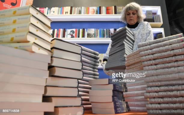 An employee of the Ullstein publishing house piles books ahead of the opening of the Frankfurt Book Fair in Frankfurt am Main western Germany on...