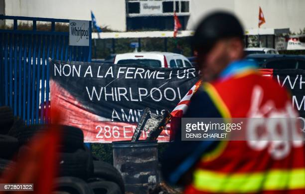 An employee of the US appliance manufacturer Whirlpool wearing an highvisibility jacket of the French General Confederation of Labour union stands...