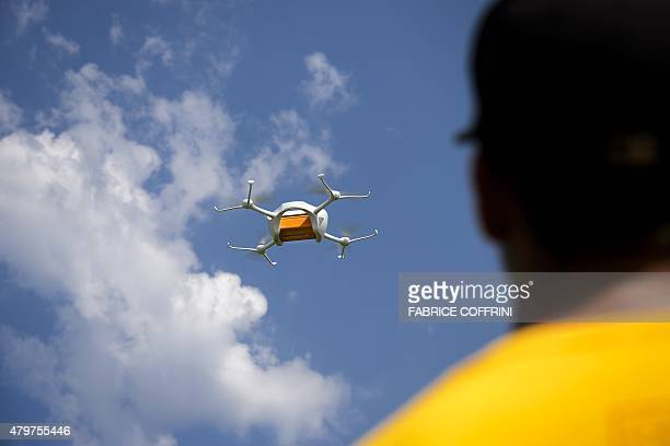 An employee of the US drone compagny Matternet shows a drone carrying a mail box of Swiss Post on July 7 2015 at the airport of Bellechasse western...