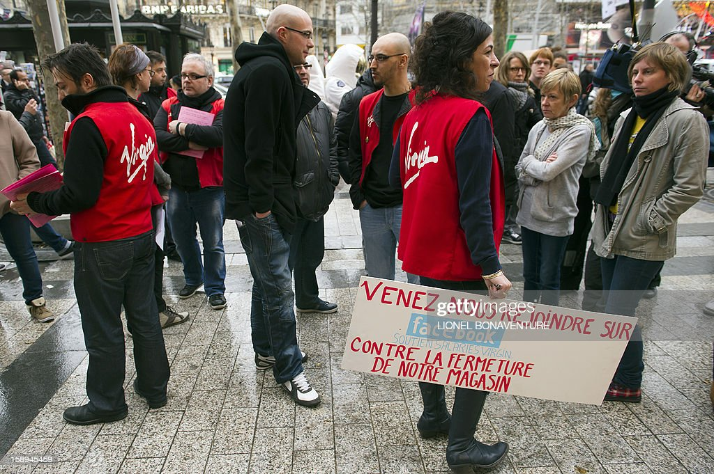An employee of the Virgin Megastore on the Champs-Elysees avenue holds a sign reading 'Come join us on Facebook in the struggle against our store's closing' as she demonstrates with co-workers against planned job cuts, at the store's entrance, on January 4, 2013, in Paris. The Virgin Megastore chain, which currently employs 1000 workers in France, is planning to file for bankruptcy and is convening an extraordinary board meeting to this effect on January 7. Originally started by Richard Branson, the British billionaire and chairman of the Virgin Group, the Virgin Megastores were bought by the French Lagardere group in 2001. AFP PHOTO / LIONEL BONAVENTURE