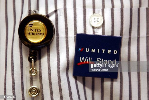 An employee of United Airline ticket counter wears a badge that says 'United will stand' at the main concorse of Denver International Airport on...