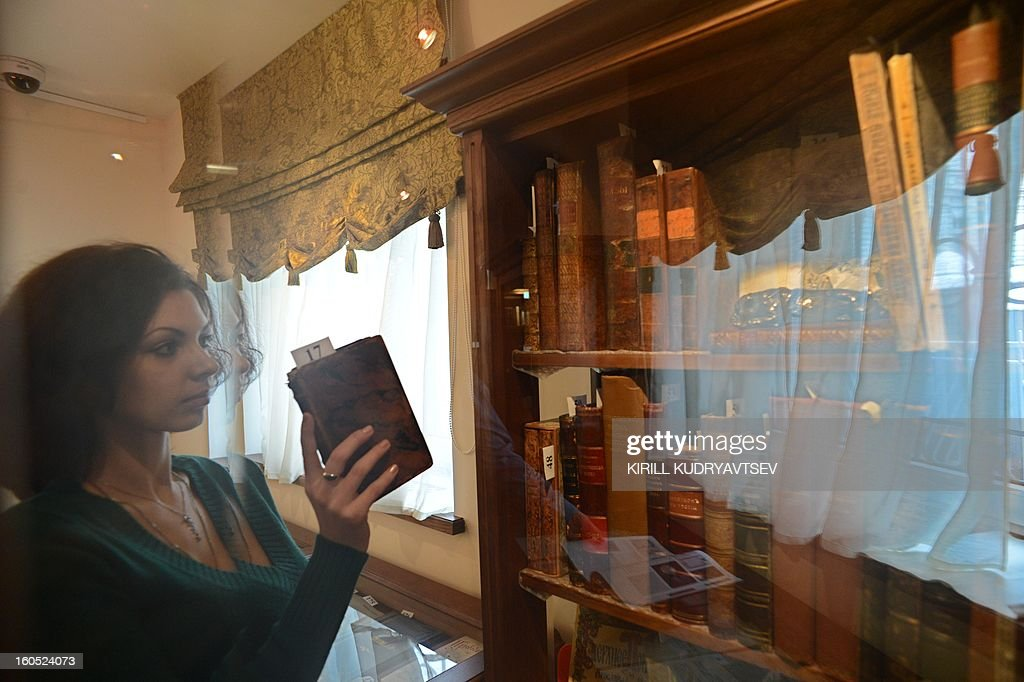 "An employee of ""V Nikitskom"" House of Antiquarian Books prepares a stand for the upcoming auction of a private collection of antique books marking the 400th anniversary of the Romanov dynasty in Moscow, on January 29, 2013."