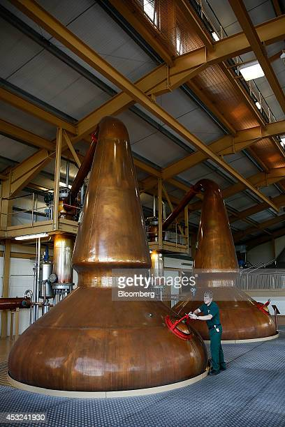 An employee opens the mandoor of a copper pot still used to distil The Glenlivet single malt whisky produced by Pernod Ricard SA at the company's...