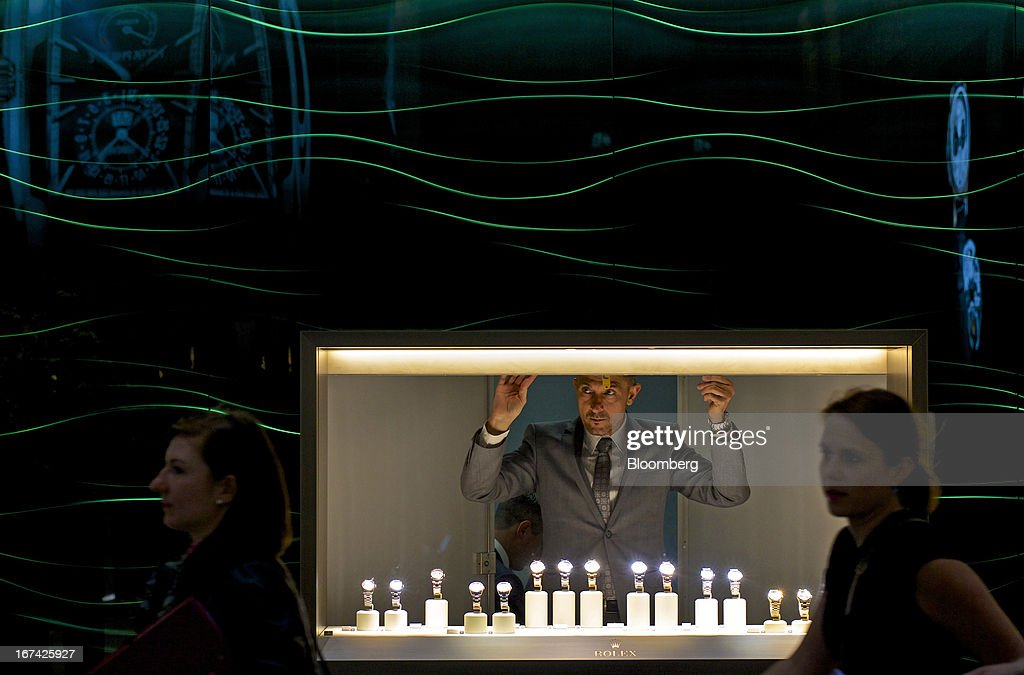 An employee opens the shutter to a display of wristwatches inside the Rolex Group booth during the Baselworld watch fair in Basel, Switzerland, on Wednesday, April 24, 2013. The annual fair attracts 2,000 companies from the watch, jewelry and gem industries to show their new wares to more than 100,000 visitors. Photographer: Gianluca Colla/Bloomberg via Getty Images