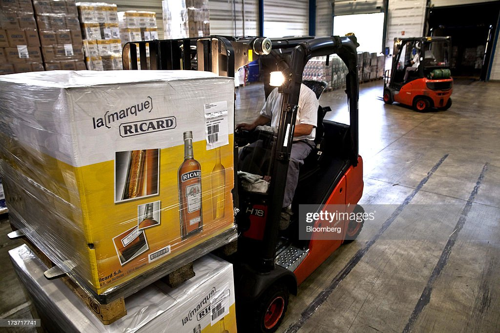 An employee operates a fork-lift truck to transport boxes containing bottles of Ricard pastis, produced by Pernod Ricard SA, at the storage area of the company's plant in Bordeaux, France, on Tuesday, July 16, 2013. Distillers such as Diageo and Pernod Ricard SA are seeking to expand in emerging markets where booming economic growth is creating a burgeoning middle class with more disposable income. Photographer: Balint Porneczi/Bloomberg via Getty Images