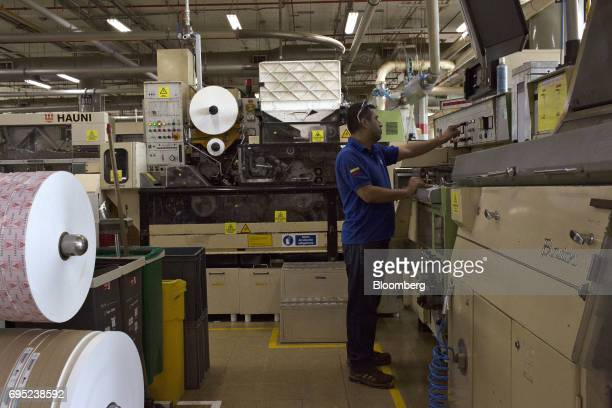 An employee operates a labeling machine at the Philip Morris International Coltabaco SAS production facility in Medellin Colombia on Friday June 2...