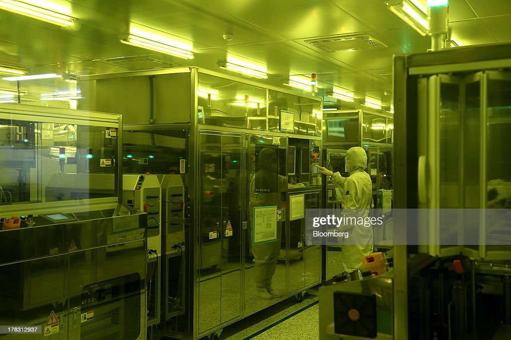 An employee operates a machine in an exposure room on the production line manufacturing Flexible Printed Circuit Boards (F-PCB) at the Seil Electronics Co. factory in Incheon, South Korea, on Wednesday, Aug. 28, 2013. South Korea has surpassed Brazil, Russia and India to become the second-biggest emerging stock market for the first time since 2006, as a stable won and record current-account surplus lure investors. Photographer: SeongJoon Cho/Bloomberg via Getty Images