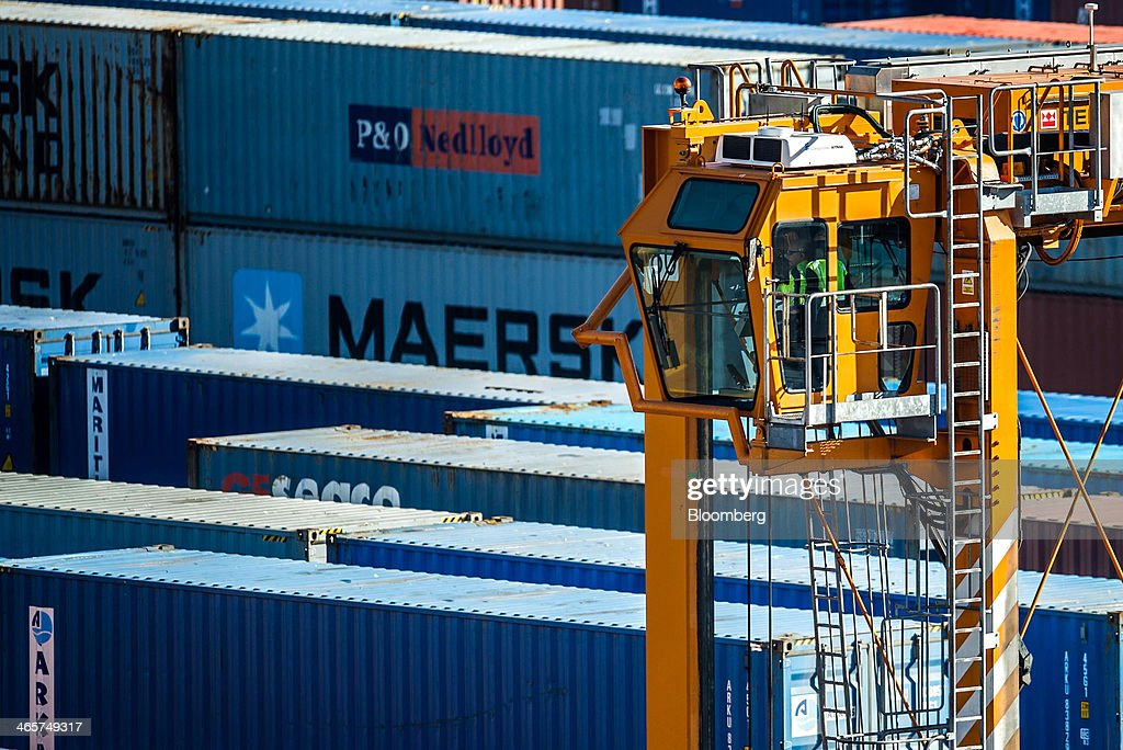 An employee operates a shipping container straddle carrier on the quayside at the commercial port in Barcelona, Spain, on Wednesday, Jan. 29, 2014. Government bonds in Europe's most-indebted countries rallied in the first three weeks of the year on signs the debt crisis that pushed those nations' borrowing costs to euro-era records had abated. Photographer: David Ramos/Bloomberg via Getty Images