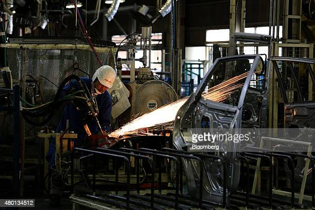 An employee operates a welding machine on a part for a Nissan Motor Co vehicle on the production line of the company's Kyushu plant in Kanda Town...