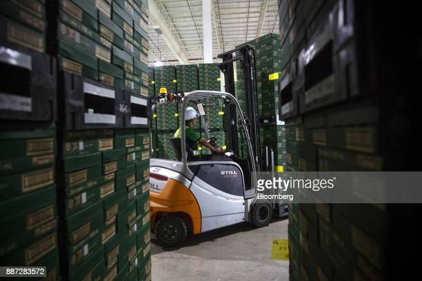 An employee operating a forklift moves a pallet of Carabao energy drink inside the warehouse at the Carabao Group Pcl plant in Chachoengsao...