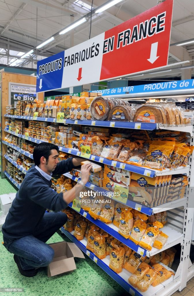 An employee organizes goods on shelves with 'Made in France' producst on January 29, 2013 in a Leclerc hypermarket in Lanester, western of France. The distribution group Leclerc test in several of his stores shelves 'made in France' requested by French Industrial Renewal Minister Arnaud Montebourg, and gives a year to 'optimize' the concept, said his boss Michel-Edouard Leclerc. AFP PHOTO / FRED TANNEAU