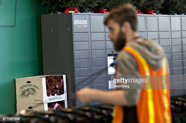 An employee organizes shopping carts in front of a wall of Amazoncom Inc lockers a selfservice parcel delivery service inside the Lakeview Whole...