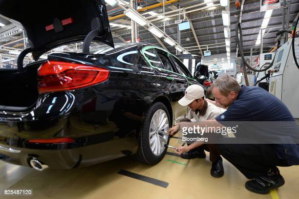 An employee overseen by a BMW launch trainer works on a BMW 530i sedan on the production line at a PT Gaya Motor plant in Jakarta Indonesia on...