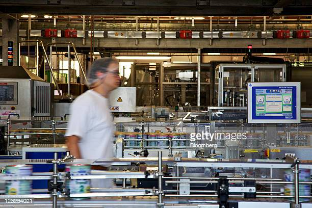 An employee oversees a conveyor belt system which fills tins with baby food supplements manufactured at Nestle's new production unit for probiotic...