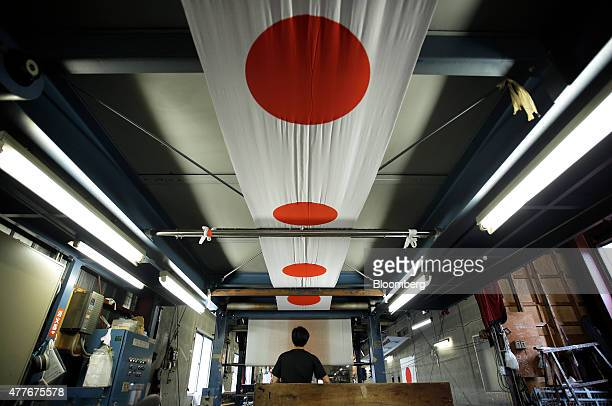 An employee oversees the drying of Japanese national flags at Tokyo Seiki Inc's manufacturing facility in Numata Gunma Prefecture Japan on Thursday...