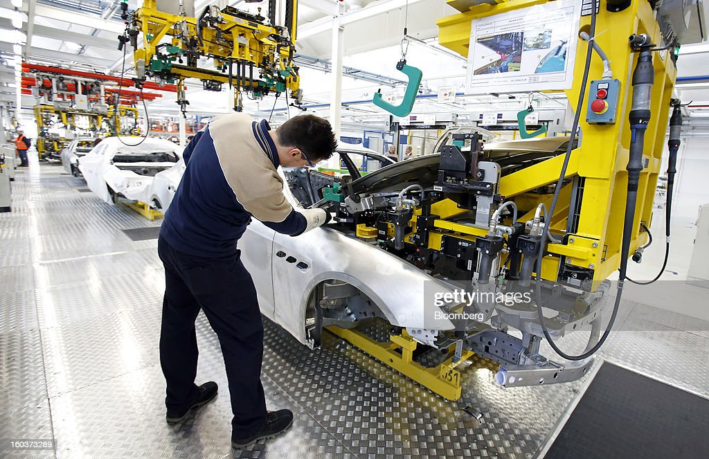 An employee oversees the robot-assisted assembly of a hood to a Maserati Quattroporte luxury automobile at Fiat SpA's Grugliasco factory in Turin, Italy, on Wednesday, Jan. 30, 2013. Fiat SpA Chief Executive Officer Sergio Marchionne said the Italian carmaker narrowed losses in Europe in the fourth quarter, helping it achieve full-year earnings that were in line with its forecasts. Photographer: Alessia Pierdomenico/Bloomberg via Getty Images