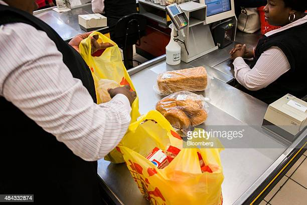 An employee packs a customer's bags with products including bread as a cashier scans the goods at the cash desk inside a Shoprite Holdings Ltd...