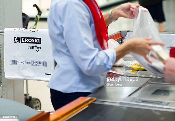 An employee packs a customer's purchases in a branded plastic carrier bag at a check out desk inside an Eroski supermarket operated by Grupo Eroski a...