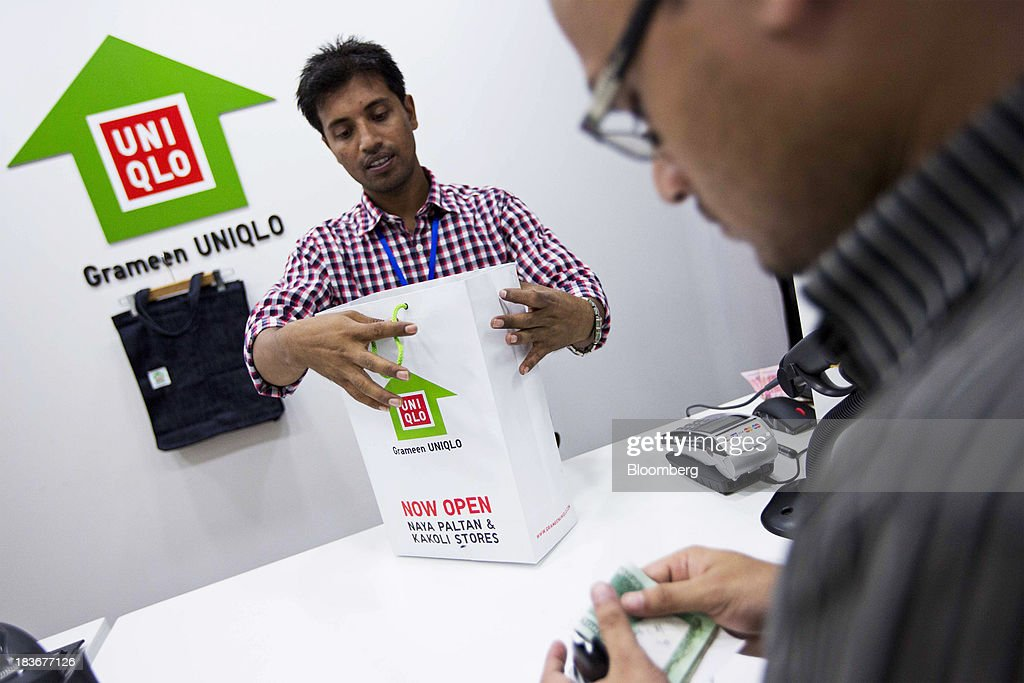 An employee packs a shopping bag of clothing for a customer at the opening of a Grameen Uniqlo store, a joint venture between Fast Retailing Co. and Grameen Healthcare Trust, in the Paltan area of Dhaka, Bangladesh, on Saturday, Oct. 5, 2013. Fast Retailing, Asia's biggest clothing retailer, set up the venture with Grameen Healthcare Trust to design, make and sell clothes in Bangladesh. Photographer: Jeff Holt/Bloomberg via Getty Images