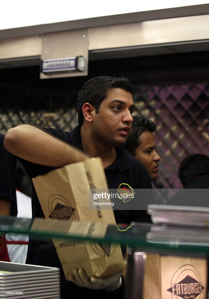 An employee packs a takeaway order at a Fatburger outlet in Karachi, Pakistan, on Saturday, Jan. 5, 2013. Fatburger opened its first outlet in Pakistan to the public on Jan. 5. Photographer: Asim Hafeez/Bloomberg via Getty Images