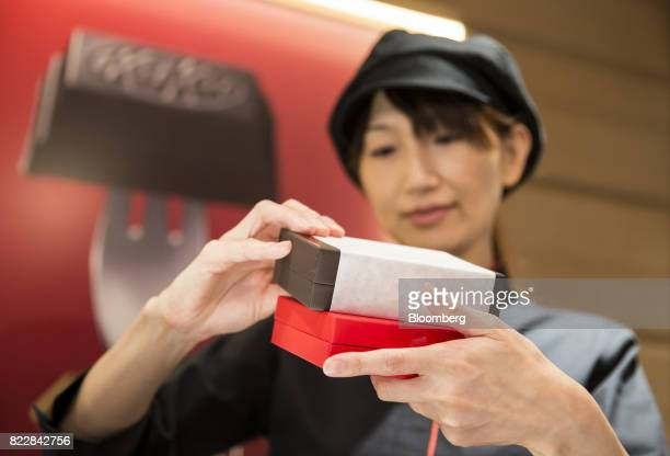 An employee packs boxes of KitKat confectionery in front of an advertisement for the Gateau Mignon KitKat during a media preview of the KitKat...