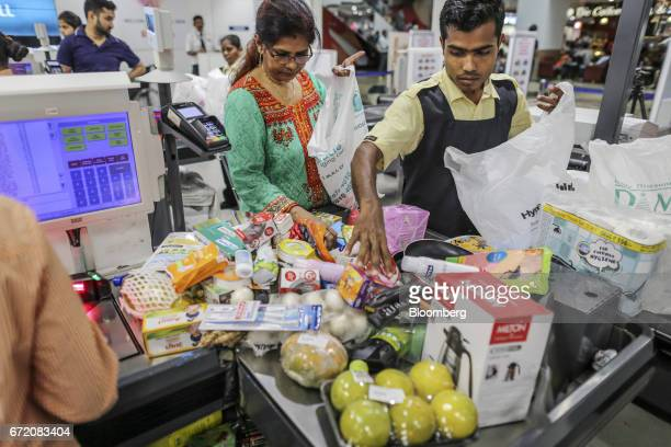 An employee packs goods into a plastic bag at a checkout counter of a Big Bazaar hypermarket operated by Future Retail Ltd in Mumbai India on Sunday...