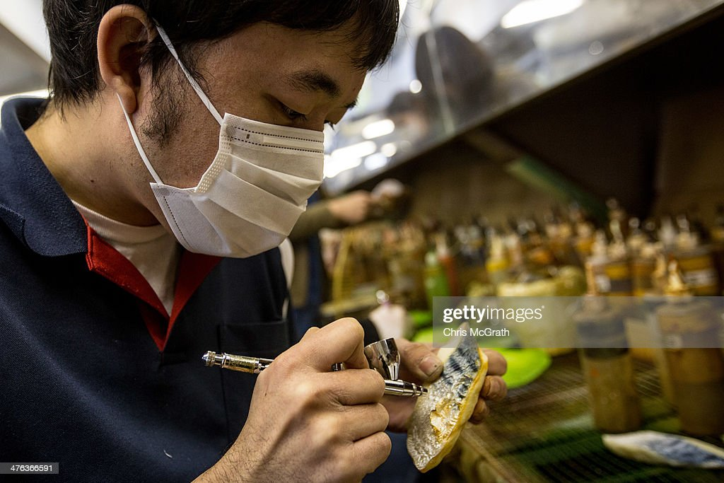 An employee paints a fish food sample made of vinyl at the Iwasaki Co., LTD sample food factory on March 3, 2014 in Yokohama, Japan. Sample food products can be seen in the windows of many restaurants throughout Japan. The factory creates precision replica food plates moulded from real food supplied by the client. The Iwasaki Co., LTD facility is one of the largest suppliers in Japan, producing approximately 270,000 sample plates per year to over 20,000 food outlets across Japan and internationally.