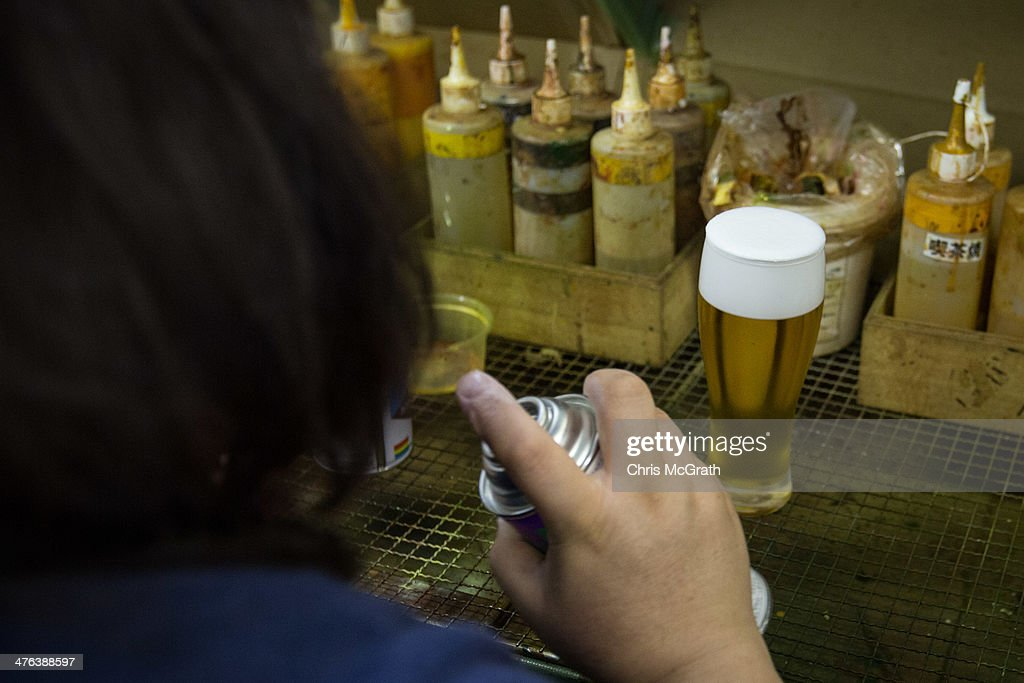 An employee paints beer food sample at the Iwasaki Co., LTD sample food factory on March 3, 2014 in Yokohama, Japan. Sample food products can be seen in the windows of many restaurants throughout Japan. The factory creates precision replica food plates moulded from real food supplied by the client. The Iwasaki Co., LTD facility is one of the largest suppliers in Japan, producing approximately 270,000 sample plates per year to over 20,000 food outlets across Japan and internationally.