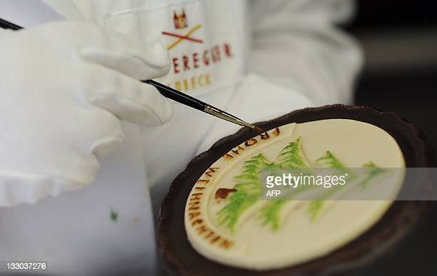 An employee paints marzipan with food color at the traditional company Niederegger in Luebeck Germany on November 9 2011 Christmas production has...