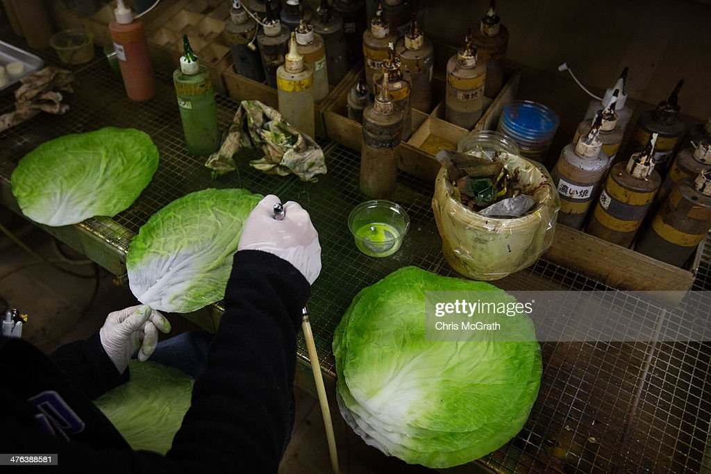 An employee paints vegetable food samples made of vinyl at the Iwasaki Co., LTD sample food factory on March 3, 2014 in Yokohama, Japan. Sample food products can be seen in the windows of many restaurants throughout Japan. The factory creates precision replica food plates moulded from real food supplied by the client. The Iwasaki Co., LTD facility is one of the largest suppliers in Japan, producing approximately 270,000 sample plates per year to over 20,000 food outlets across Japan and internationally.