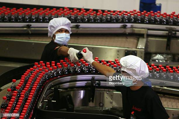 An employee passes a bottle of CocaCola soda to another employee as they inspect bottle labeling on the production line at the CocaCola Co bottling...