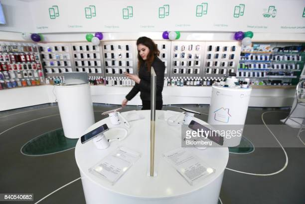 An employee passes a display of Apple Inc smartphones including iPhone SE left and 7 Plus right models inside a MegaFon PJSC mobile phone store in...